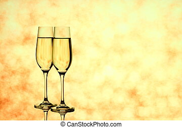 Two champagne glasses on blurred golden background