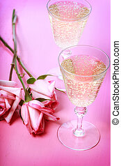 Two champagne glasses with pink roses