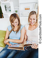 Two charming female friends looking at a photo album together on a sofa at home