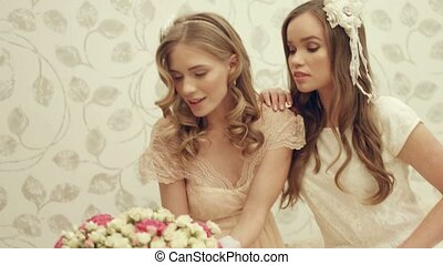 Two charming girls in dresses posing with a big bouquet of roses in a box at a photo shoot