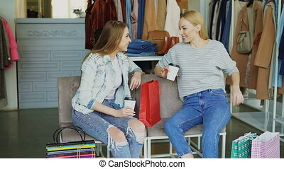 Two charming girls sitting in clothes shop with coffee,...