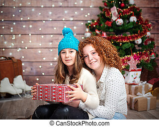 Two charming little girls, sisters with a New Year's gift in their hands.