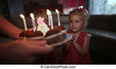 Two charming twin sisters in beautiful red dresses are waiting for a cake with burning candles. They blow candles and clap their hands, hugging each other.