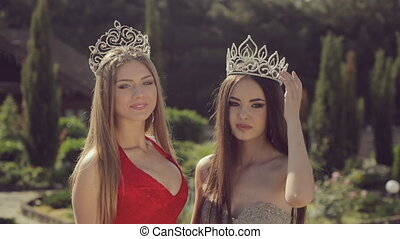 Two charming young girls in evening gowns and crowns smiling...