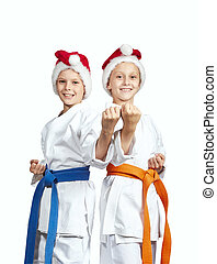 Two cheerful athlete standing in the rack of karate