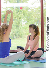 two cheerful attractive fit women doing yoga at home