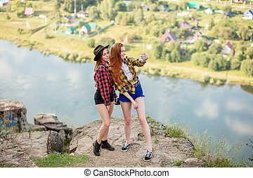 Two cheerful beautiful female hikers taking selfie on top of the mountain