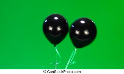 two cheerful black balloon with eyes and a smile on green