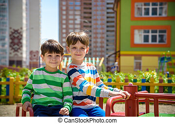 two cheerful boys in t-shirts play on a big iron carousel on the playground at the summer or spring warm day in kindergarten. Kids has a lot of fun. Friendship concept