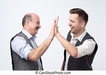Two cheerful business men clapping each other hands and smiling