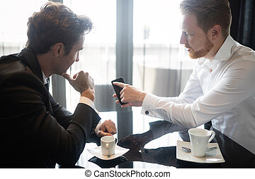 Two cheerful business people in formalwear discussing something and one of them pointing mobile