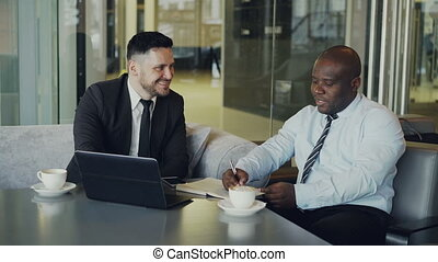 Two cheerful businessmen discussing project in modern cafe. African American entrepreneur writing in notebook and his caucasian partner in business suit pointing at laptop computer