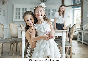 Two cheerful daughters posing with mother