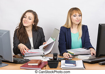 Two cheerful employee of the office sitting at a desk and working with documents