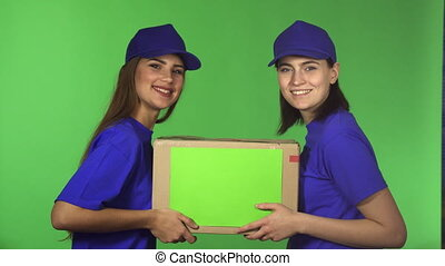 Two cheerful female delivery service workers smiling holding cardboard box