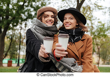 Two cheerful girls dressed in autumn clothes