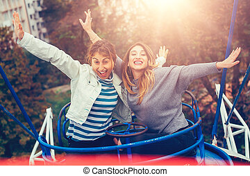 Two cheerful girls having fun on merry go round at amusement...