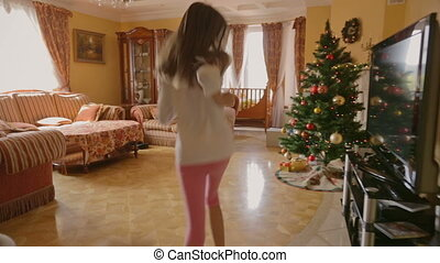 Two cheerful girls in pajamas running to presents under the Christmas tree at morning