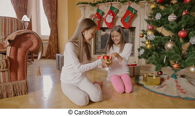 Two cheerful girls in pajamas sitting under Christmas tree and opening boxes with presents