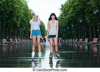 Two cheerful girls rollerblading