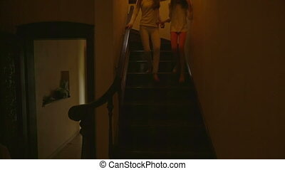 Two cheerful girls running from the house second floor to the living room to open Christmas gifts