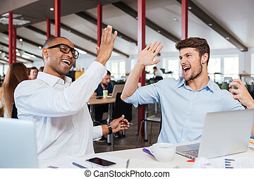 Two cheerful men giving high five and working in office