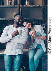 two cheerful mixed race people drink tea. Handsome afro american guy together with his beautiful caucasian girl in kitchen