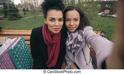 Two cheerful mixed race woman with shopping bags talking at video call with smartpone. Young girls sitting on bench have online chat with friends