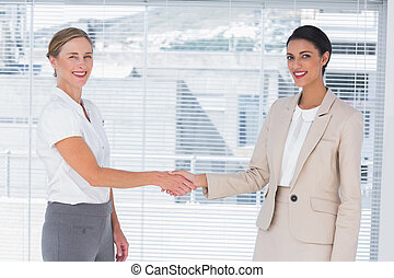 Two cheerful partners shaking hands