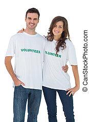 Two cheerful people wearing volunteer tshirt on white...