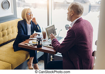 two cheerful senior people having a chat in the modern cafe