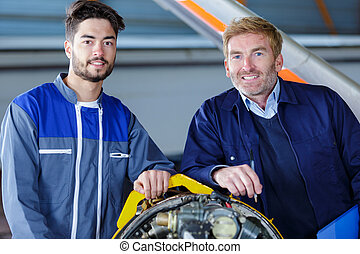 two cheerful smiling mechanics posing together