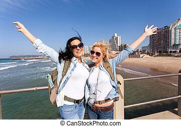 cheerful tourists by beachfront