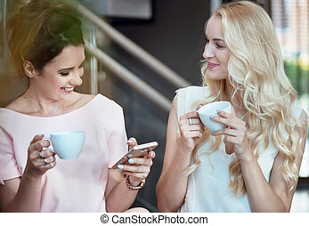 Two cheerful women drinking coffee and looking at the smartphone
