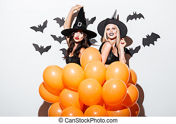 Two cheerful women in witch costumes dancing with orange...