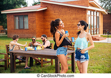 Two cheerful women talking and laughing on summer outdoor party