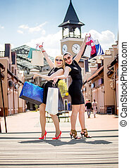 Two cheerful women with shopping bags posing on street