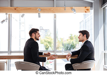 Two cheerful young businessmen having business meeting