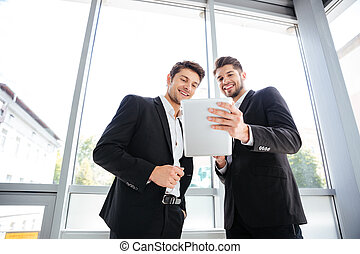 Two cheerful young businessmen using tablet in office together
