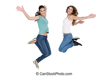 Two cheerful young female friends jumping