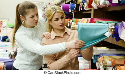 Two cheerful young female friends looking for interesting cloth in textile shop
