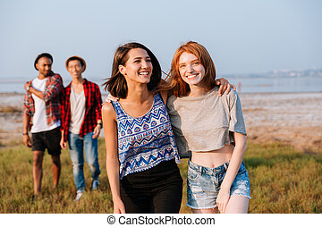 Two cheerful young men and women laughing outdoors