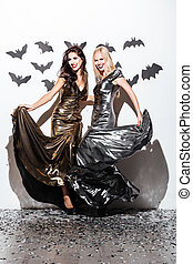 Two cheerful young women with halloween vampire makeup on...
