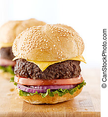 Two cheeseburgers on a wooden surface.
