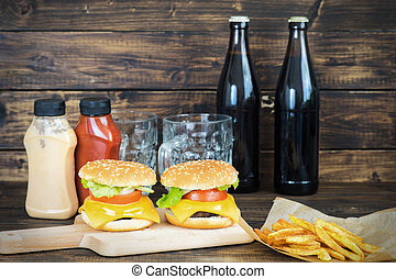 Two cheeseburgers with two bottles of dark beer