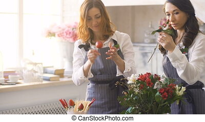 Two chef woman and florist preparing flowers, fruits and...