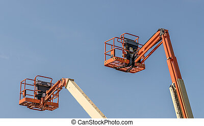 Two Cherry Picker machines against a blue sky