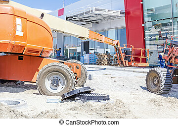 Two cherry pickers are parked at building site. Low angle view