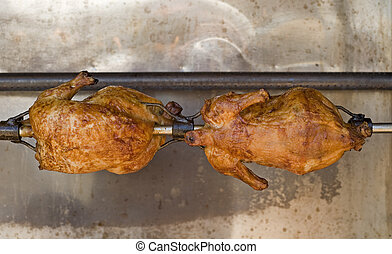 Two chickens roasting on a spit
