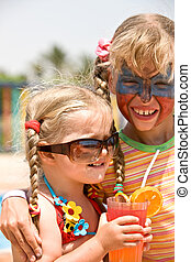 Two child girl with paint on face drink  juice.